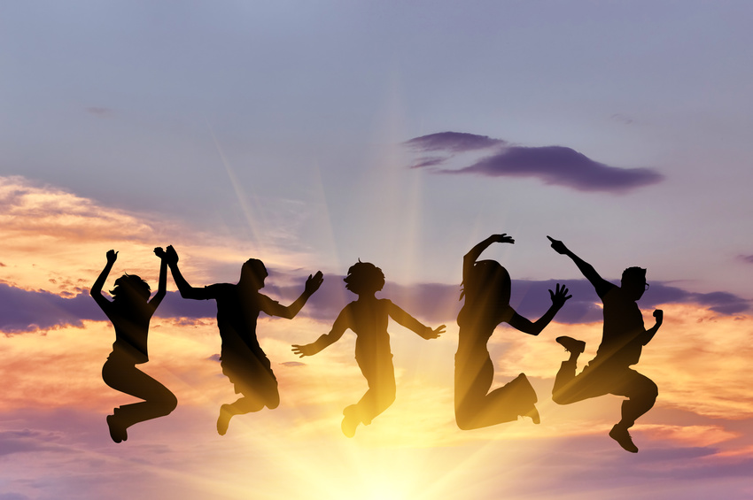 Concept of emotion. Silhouette of a happy group of people jumping at sunset