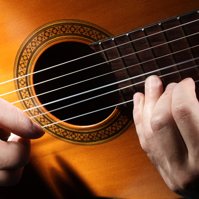 Acoustic guitar string music. Guitarist playing. Details of musical instrument with performer hands